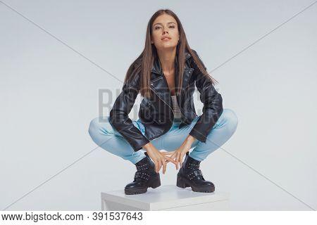 Positive fashion model smiling, wearing leather jacket while crouching on gray studio background
