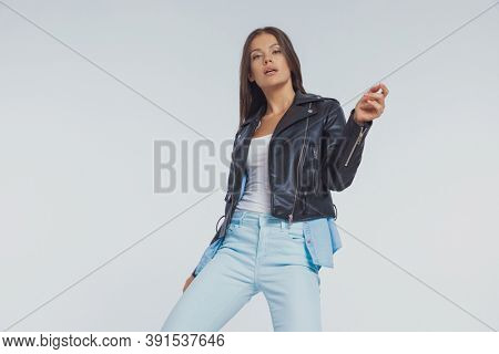 Bossy fashion model snipping her fingers, wearing leather jacket while standing on gray studio background