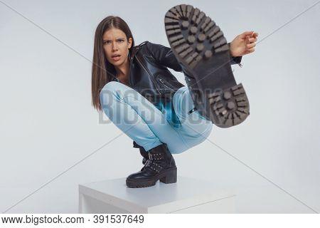 Tough fashion model kicking with her leg, wearing leather jacket while crouching on gray studio background