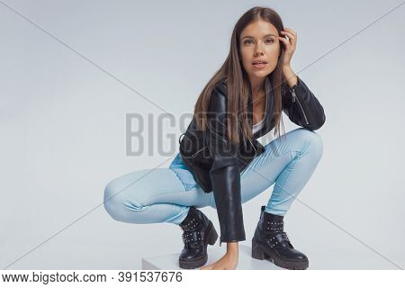 Focused fashion model adjusting her hair, wearing leather jacket while crouching on gray studio background