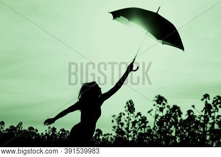 Unplugged Free Silhouette Woman With Umbrella Up To Green Sky. Nature Girl At Windy Rainy Day Has Ad