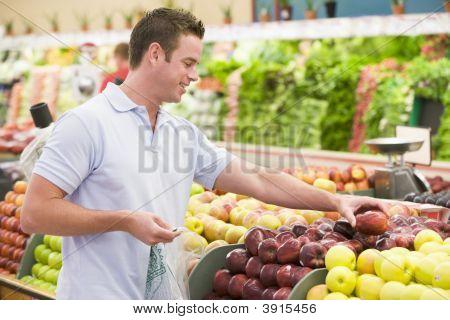 Man Choosing Fruit In Shop