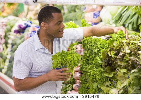 Man Choosing Vegetables In Shop