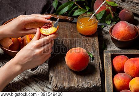 Woman Hands Cuts Peaches For Making Recipe For Jam, Dessert, Juice On Rustic Cutting Board. Peaches