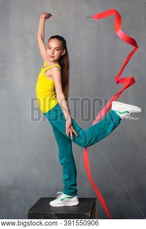 Gymnast With Ribbon. The Gymnast Raises Her Leg High. Good Stretch. Sportswoman In A Tracksuit. Gymn