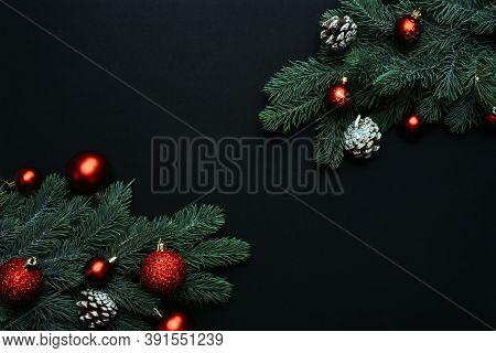 Red Christmas Balls On Branches Of A Christmas Tree On A Black Background. Place For Text Between Ch