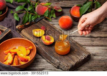 Peach Jam Spoon In Female Hand. Canned Fruit Jam Glass Jar With Peach Wedges And Whole Fruit. Peach