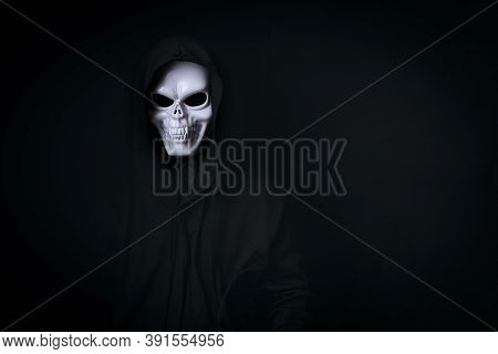 Man In Spooky Dead Skull Cosplay In Black Dressed For Halloween Festival On Black Background Acting