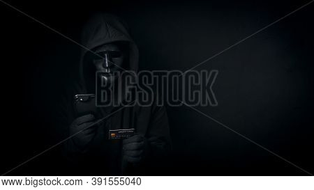Dangerous Anonymous Hacker Man In Hooded And Mask Use Smartphone And Credit Card, Break Security Dat