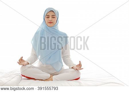 Close Up Young Asian Arab Woman Sitting On Bed And Enjoying Meditation. Beautiful Muslim Girl In Sle