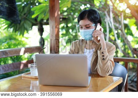 Young Asian Woman In Casual Dress With Face Shield And Protect Mask For Healthcare, Sitting In Coffe