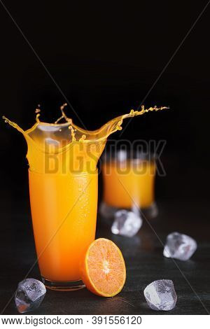 Fresh Homemade Orange Juice In Glass With Ice On Vintage Wooden Table. Freshness Beverage With Splas