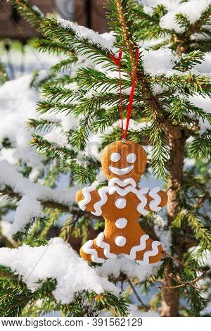 A Christmas Tree Toy In The Shape Of A Gingerbread Man Decorates A Green Christmas Tree Covered With