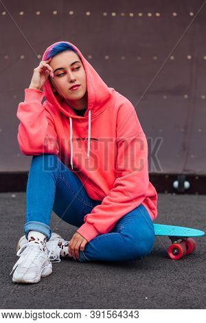 Portrait Of A Trendy Pretty Young Girl Sitting Next To The Skateboard Court On Her Plastic Skateboar