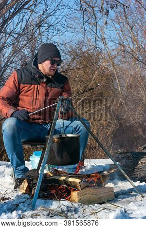 Male Caucasian Is Sitting By Campfire, Pot Of Soot Over Bonfire Hanging On Tripod, Winter Outdoor Co