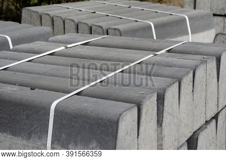 New Curbs Are Tied With White Bondage Tape In An Outdoor Warehouse. Concrete Curbs On Wooden Pallets