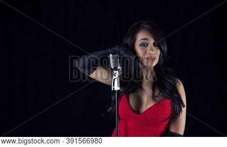 Beautiful Black Singer Woman. With Retro 50s Microphone And Red Low Cut Dress