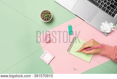 Feminine Workplace Concept. Items On Bright Pink And Green Background, Top View. Female Hand Makes A