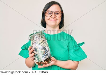 Brunette woman with down syndrome holding jar with savings smiling with a happy and cool smile on face. showing teeth.