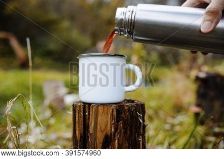Person Pours Hot Tea From A Thermos Into A Mug. Cropping, Close-up. Concept For Outdoor Activities,