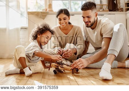 Happy Multiethnic Family Parents And Boy Playing With Toy Plane  On Floor In Cozy Kitchen At Home