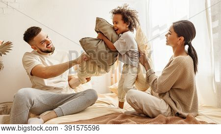Happy Family Multiethnic Mother, Father And Son  Laughing, Playing, Fights Pillows And Jumping In Be