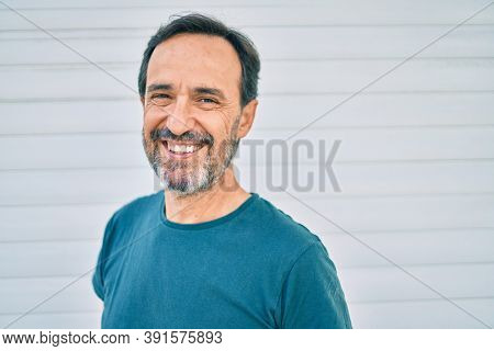 Middle age man with beard smiling happy outdoors leaning on the wall