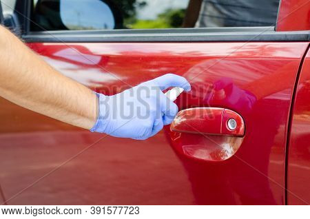 Man Sanitizing Door Handle Of His Car Outdoors.  Male Hand In Protective Glove Holding Sanitizer Clo