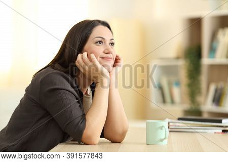 Dreamer Dreaming Looking Away In A Desk In The Living Room At Home