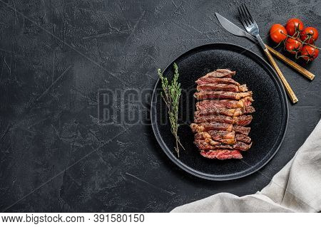 Sliced Rib Eye, Ribeye Steak On A Plate With A Sprig Of Thyme. Black Background. Top View. Copy Spac