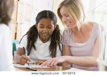Teacher Helping Pupils In Classroom