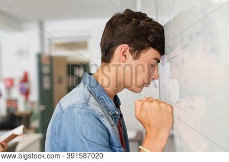 Disappointed university student leaning on whiteboard with closed eyes. Tired high school guy feeling failure in classroom. Side view of sad young college student trying to solve math problem.