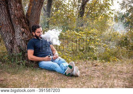 Stylish Brutal Smoker Enjoying An Electronic Cigarette In The Daylight. Hybrid Cigarette.