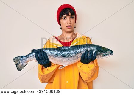 Beautiful brunettte fisher woman wearing raincoat holding fresh salmon clueless and confused expression. doubt concept.