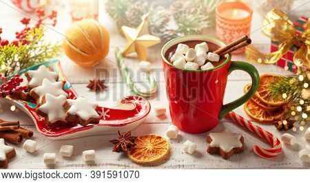 Concept Christmas homemade food and drink. Hot chocolate with marshmallows and cinnamon in red cup, Christmas cookies, winter spices and festive decor on wooden table.