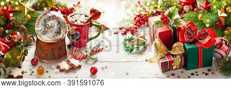 Composition with Christmas snow globe, gift boxes, cup of hot chocolate and festive decorations on wooden table. Christmas or New Year concept