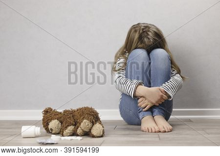 Sad Teenager Girl, Schoolgirl In Depression Sits On The Floor Near The Wall, Next To A Teddy Bear An