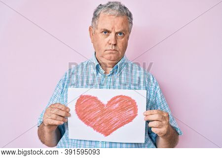 Senior grey-haired man holding heart draw relaxed with serious expression on face. simple and natural looking at the camera.