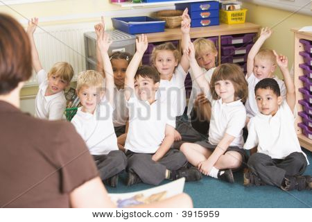 Teacher Reading Book To Children Sat On Carpet
