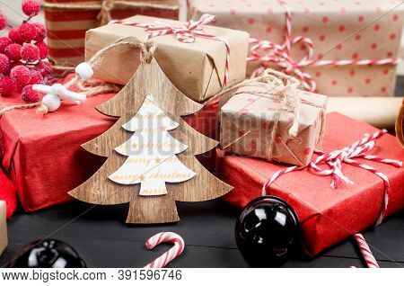 Crafted Christmas Handmade Presents Wrapped In Craft Paper, Scrolls And Xmas Decoration On Wooden Ba