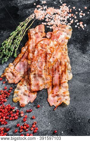 Cooked Sizzling Hot Tasty Crispy Bacon. Black Background. Top View