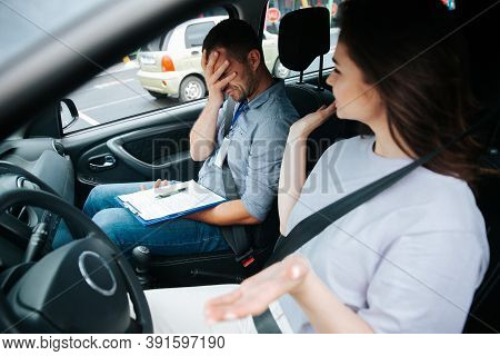Attractive Female Driver In White Shirt Turns Her Head To Upset Male Auto Instructor Making Facepalm