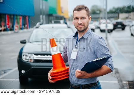 Male Driving Instructor Standing With Orange Traffic Cones And Clipboard In His Hands. Caucasian Man