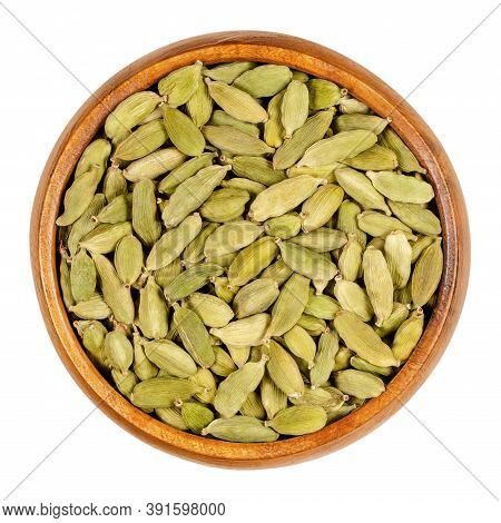 Green Cardamom Pods In A Wooden Bowl. True Cardamom, Processed Pods And Seeds Of Elettaria Cardamomu