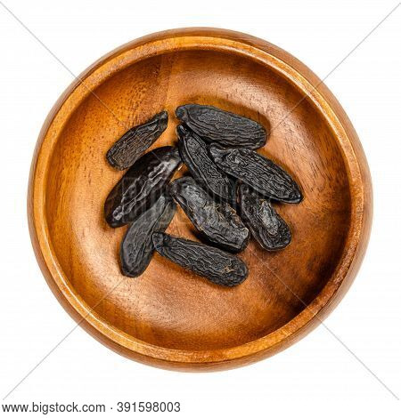Tonka Beans In A Wooden Bowl. Tonkin Or Tonquin Beans, Black And Wrinkled Seeds Of The Tree Dipteryx