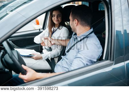 Female Auto Instructor Shaking Hands With Male Student. Attractive Woman Congratulates With Successf