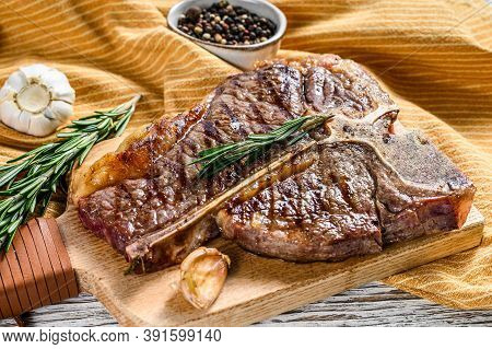 Grilled Porterhouse Steak On A Chopping Board. Cooked Beef Meat. White Wooden Background. Top View