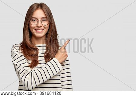 Waist Up Shot Of Pretty Caucasian Woman With Cheerful Expression, Points With Index Finger At Blank