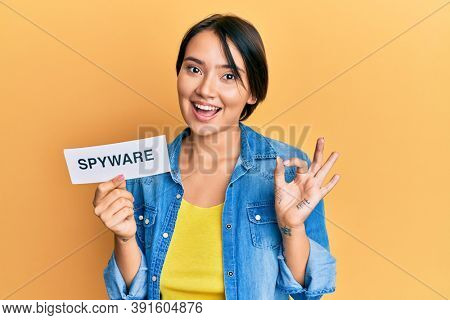 Beautiful young woman with short hair holding spyware text doing ok sign with fingers, smiling friendly gesturing excellent symbol