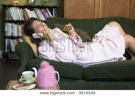 Woman Sat On Sofa With Phone And Chocolate